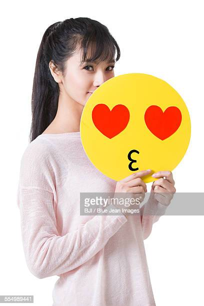 Young woman holding a romantic emoticon face