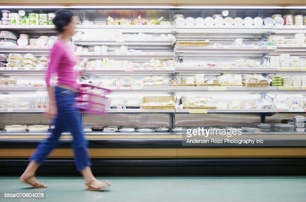 Young woman holding a shopping basket walking past isles in a supermarket (blurred)