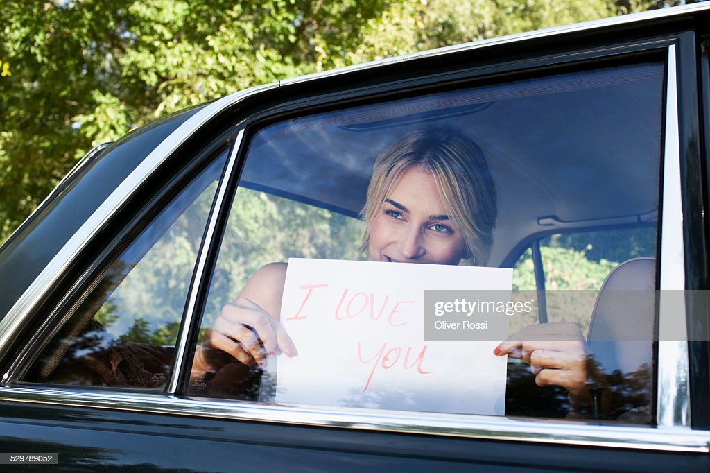 Young woman holding a sign saying 'I Love You' up to a car window : Stock-Foto