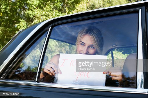 Young woman holding a sign saying 'I Love You' up to a car window : Stockfoto
