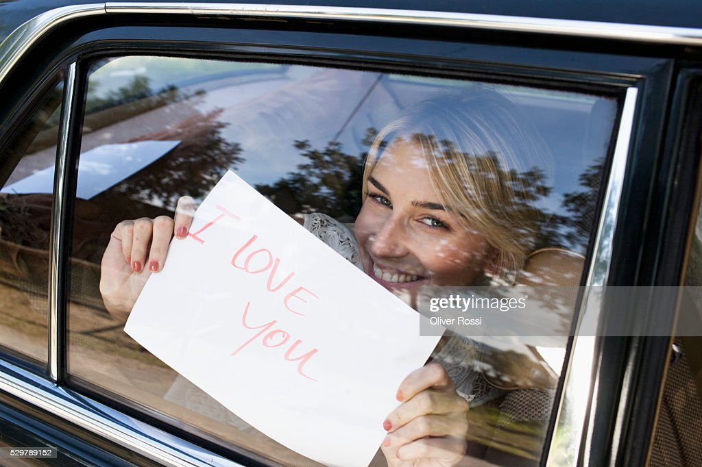 Young woman holding a sign saying 'I Love You' up to a car window : Foto de stock