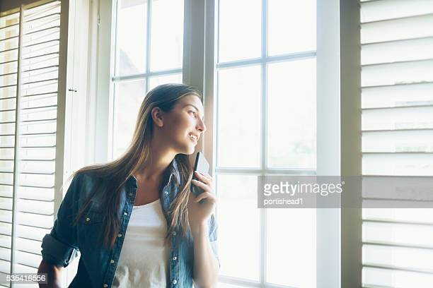 Young woman holding a smart phone and looking through window