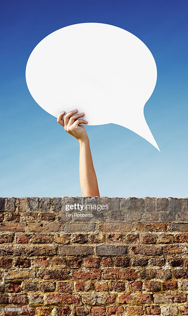 Young woman holding a speech bubble above a wall. : Stock Photo