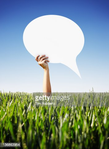Young woman holding a speech bubble above crops. : Stock Photo