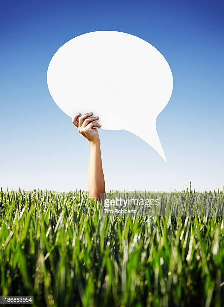 Young woman holding a speech bubble above crops.