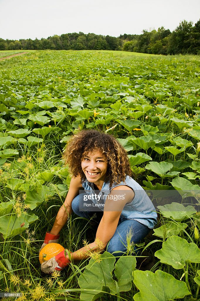 Young woman holding a squash at an Organic farm : Stock Photo