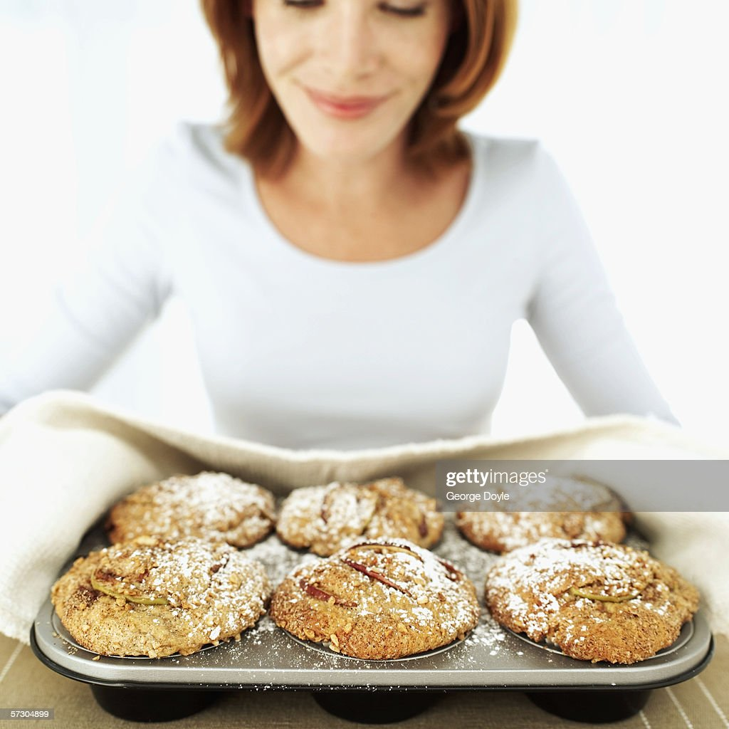 Young woman holding a tray of freshly baked muffins