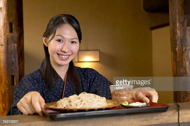 Young woman holding a tray of noodles