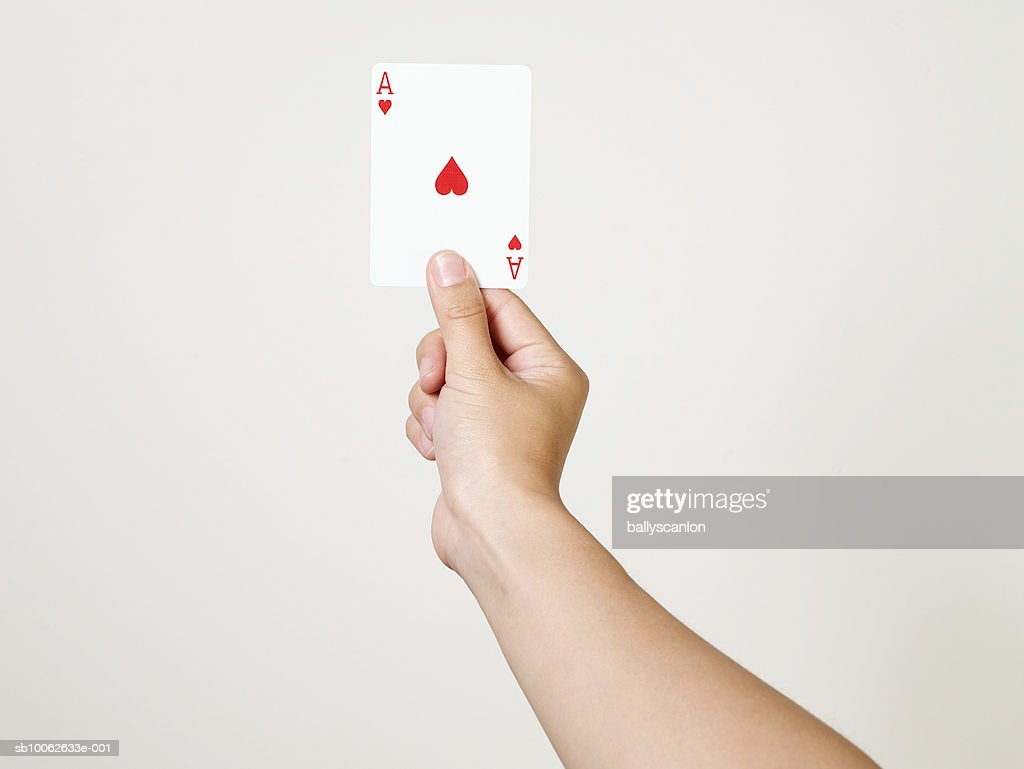Young woman holding ace of hearts playing card, close-up of arm and hand, studio shot : Bildbanksbilder