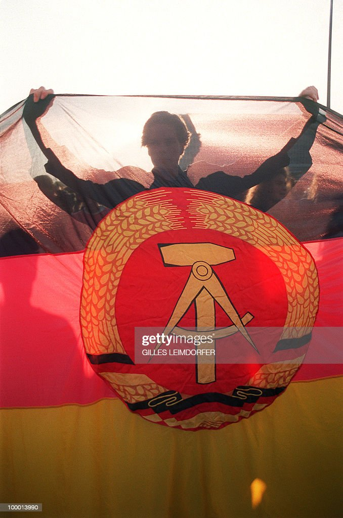 A young Berliner girl, brandishing an East German flag - one with the defunct hammer and compass crossed out - stages a rally, among several thousand others, 03 October 1990 at Alexander Platz in East Berlin against the country's reunification chanting, 'Shut your mouth Germany, that's enough'. Forty-five years after the end of the Second War, Germany was free and united in liberty 03 October 1990, only 11 months since the Berlin Wall dividing East, German Democratic Republic, and West, Federal Republic of Germany, began to disintegrate.