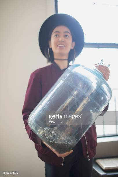 A young woman holding an empty water tank