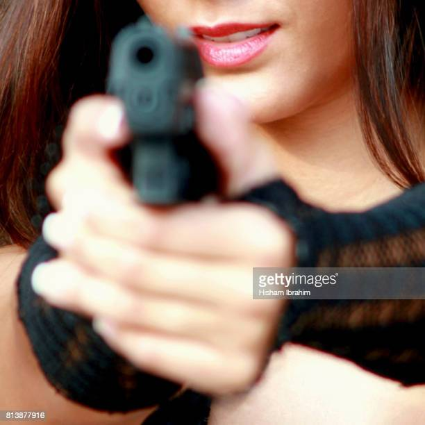 Young woman holding and Aiming a hand held gun.