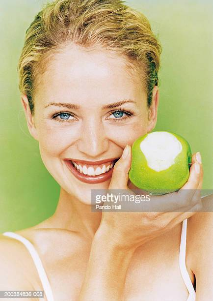 Young woman holding apple missing bite, smiling, close up, portrait