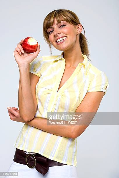 Young woman holding apple, portrait, close-up