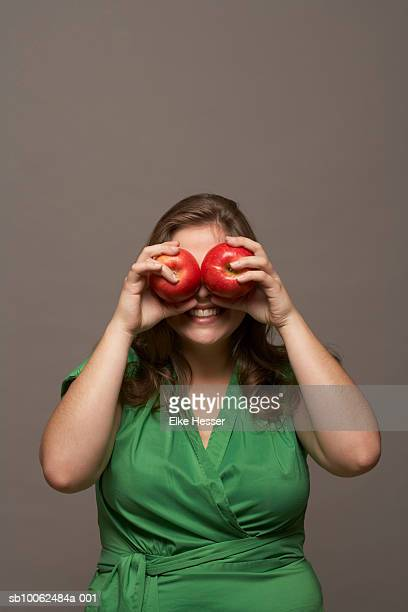 Young woman holding apples over eyes, upper half