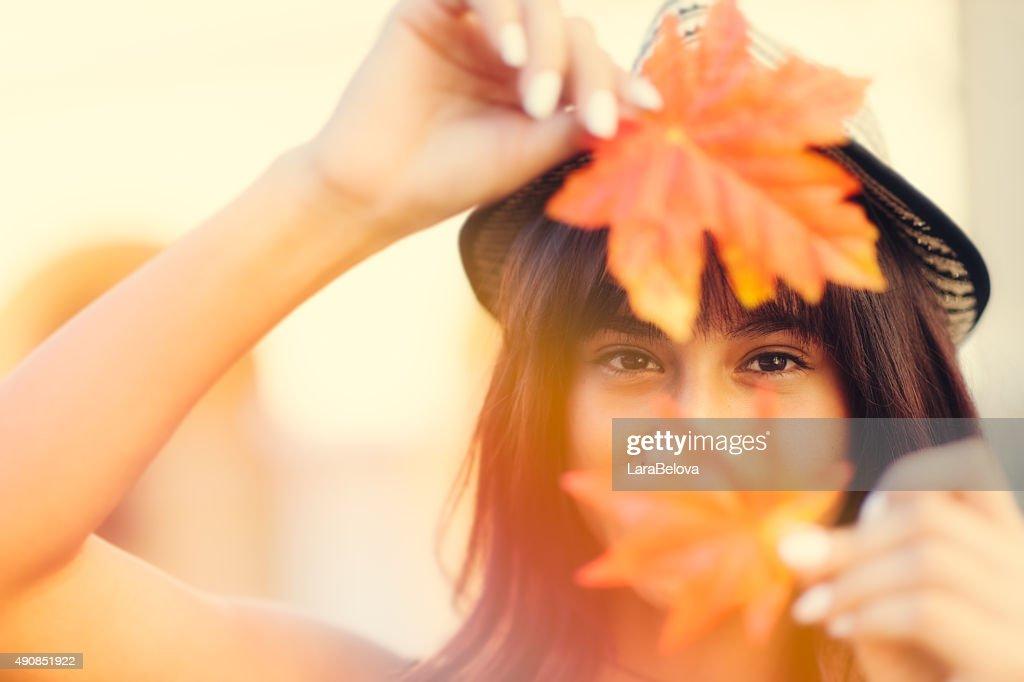 Jeune femme tenant l'automne leafs dans les mains : Photo