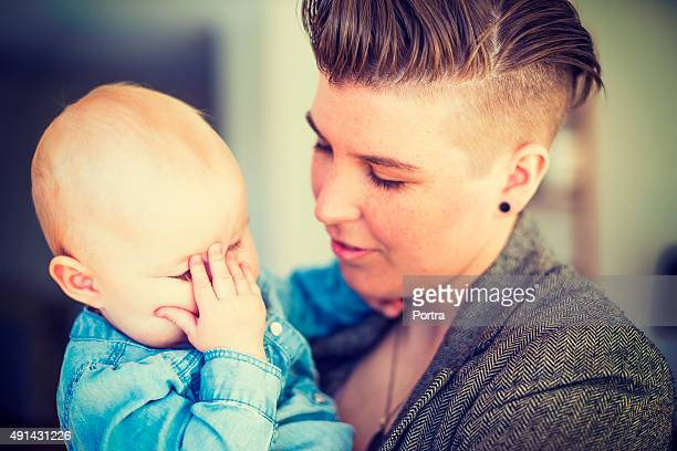 Young woman holding baby with hand on face at home