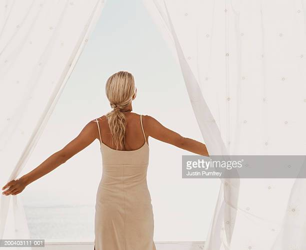 Young woman holding back curtains, arms outstretched, rear view
