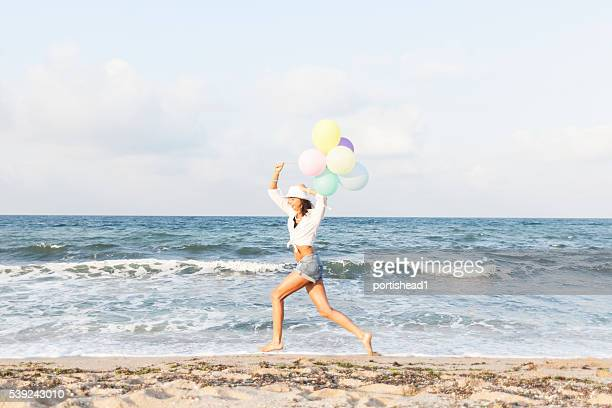 Young woman holding balloons and running on beach