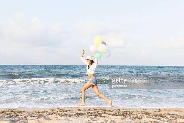 Junge Frau hält Luftballons und laufen am Strand
