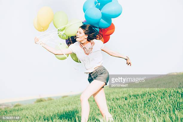 Young woman holding balloons blown away by the wind-side view