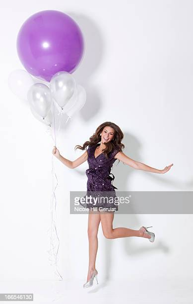 Young woman holding balloons, floating at party