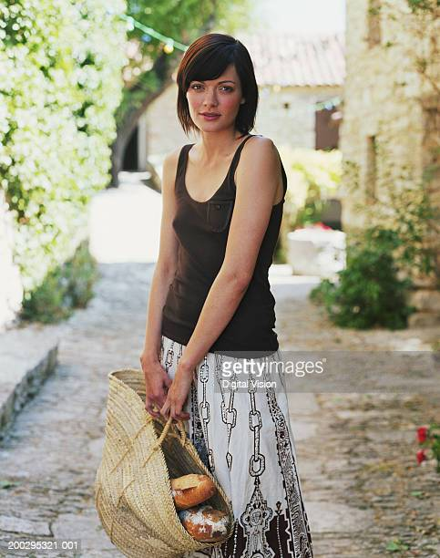 Young woman holding basket of bread, portrait