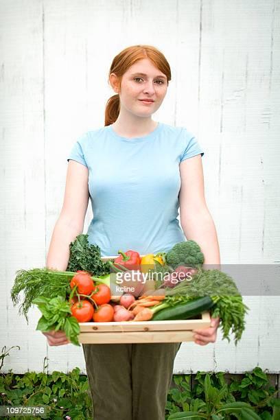 Giovane donna con cesto di verdure fresche sul giardino