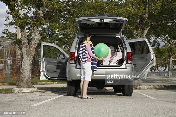 Young woman holding beach ball in back of SUV, side view