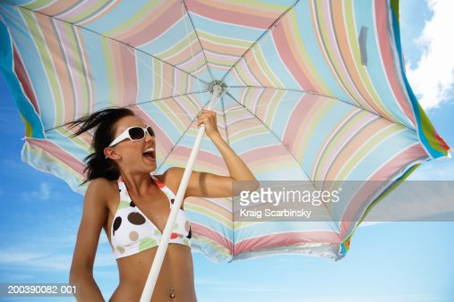 Young woman holding beach umbrella, laughing, low angle view