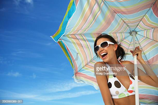 Young woman holding beach umbrella, smiling, close-up