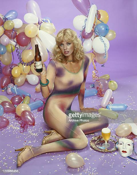 Young woman holding beer bottle besides balloon decoration, portrait