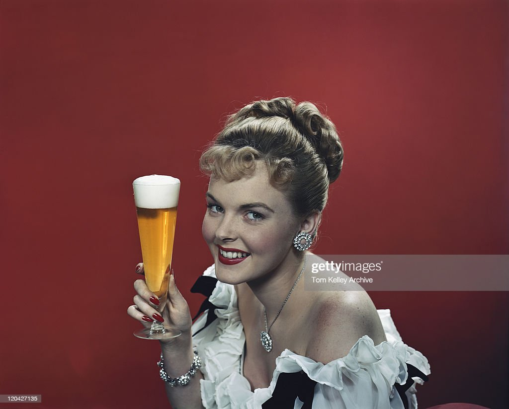 Young woman holding beer glass, smiling, portrait : Stock Photo