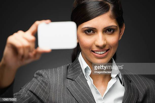 Young woman holding blank card