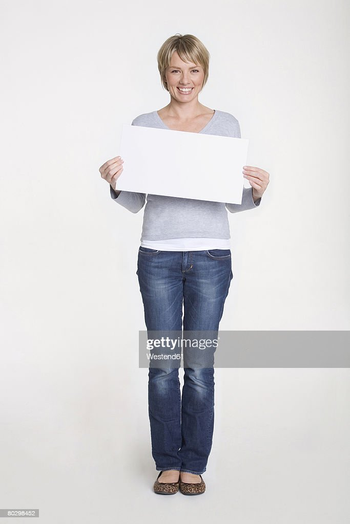Young woman holding blank white board, portrait : Stock-Foto