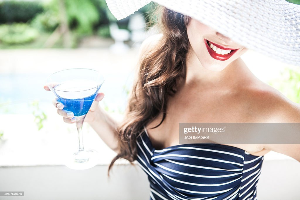 Young woman holding blue cocktail