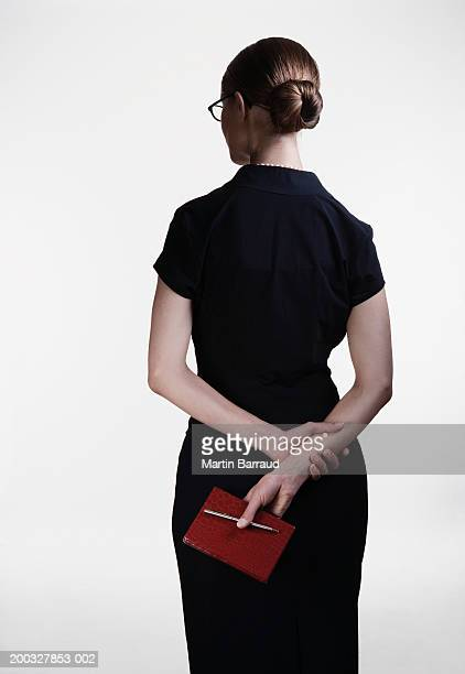 Young woman holding book and pen behind back, rear view