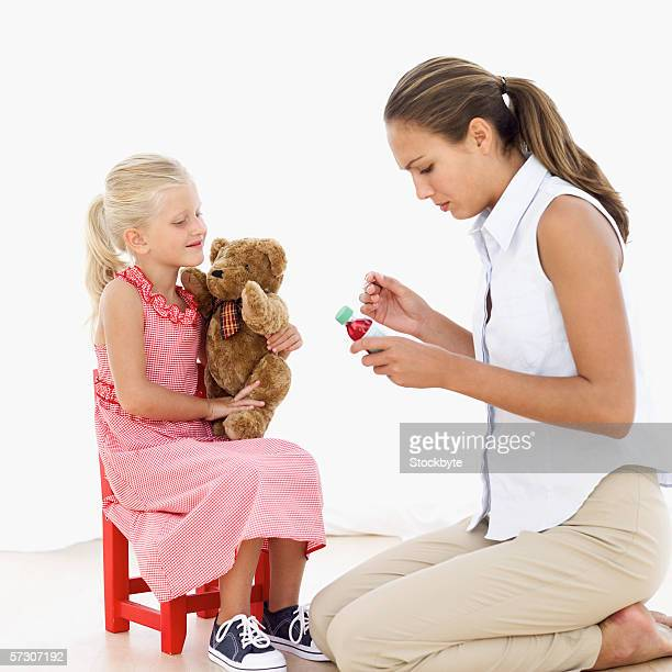 Young woman holding bottle of medication and young girl (6-8) sitting on chair holding teddy bear