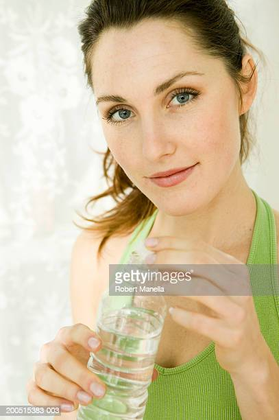 Young woman holding bottle of water, portrait