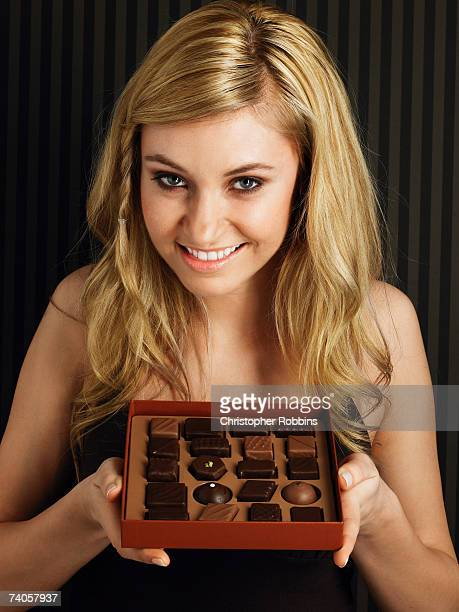 Young woman holding box of chocolates, smiling, portrait