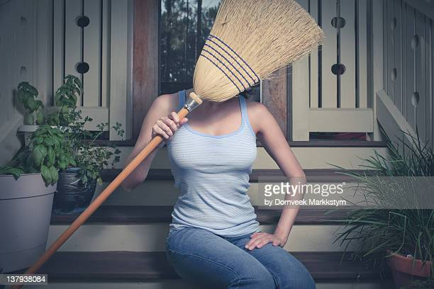 Young woman holding broom over her face