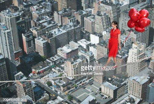 Young woman holding bunch of balloons, on tightrope over cityscape : Stock Photo