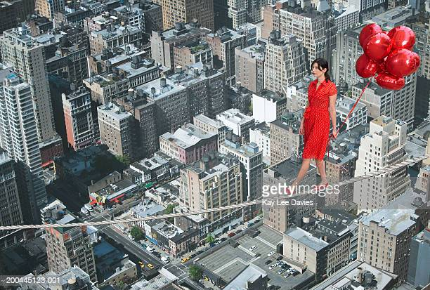 Young woman holding bunch of balloons, on tightrope over cityscape