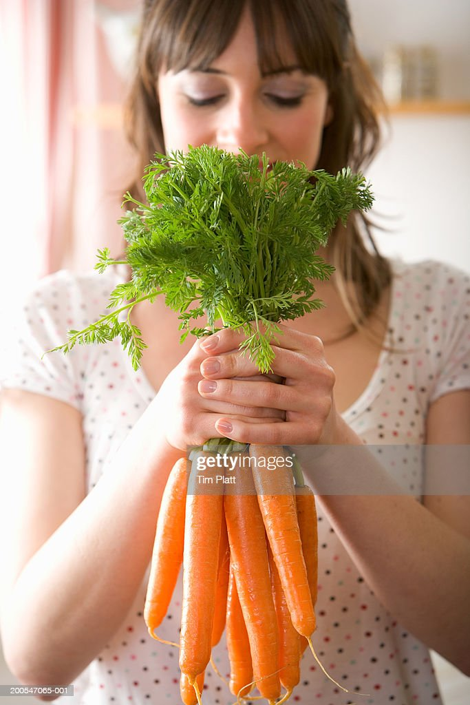 Young woman holding bunch of carrots, close-up : Stock Photo