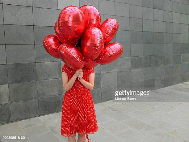 Young woman holding bunch of red foil balloons, face obscured