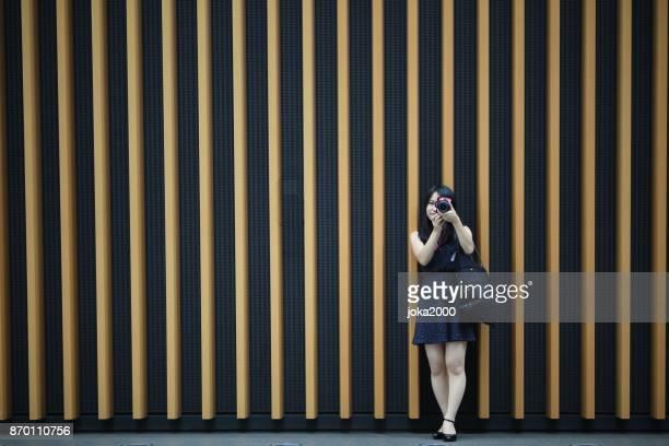 壁の前にカメラを保持している若い女性