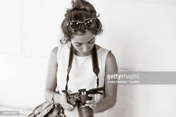 Young Woman Holding Camera While Standing By Wall