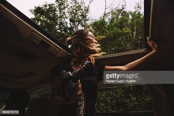 Young Woman Holding Camera While Standing In Car With Sun Roof