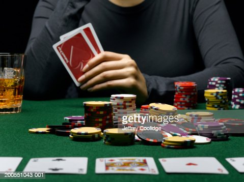 Young woman holding cards at poker table, mid section