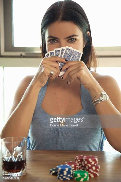 Young woman holding cards up to face, poker chips on table